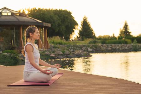 Woman meditating near lake on sunset