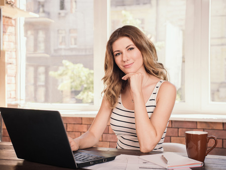 Photo pour Portrait of a beautiful business woman smiling and sitting near table screen - image libre de droit