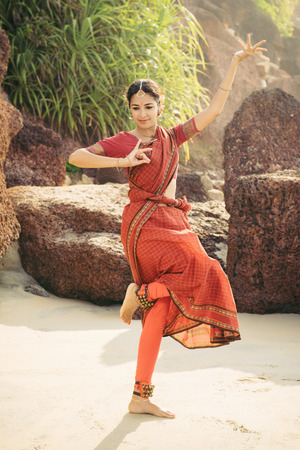 Photo pour Beautiful indian woman in red saree dancing traditional Bharatanatyam dance - image libre de droit