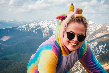 Funny travel concept. Hiker wearing sunglasses and unicorn suit on the Carpathian mountain background on a Spring day. Looking at camera. Wanderlust.