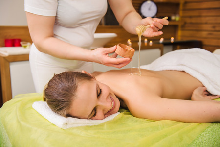 Photo pour Beautiful young woman receiving spa treatment with honey. Body and health care concept. - image libre de droit