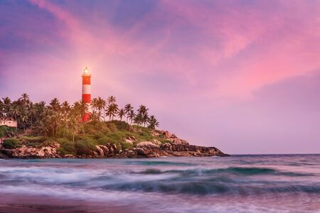 Photo pour Lighthouse on the cliff surrounded by palm trees and blurred sea waves on the Kovalam beach. Kerala, India - image libre de droit