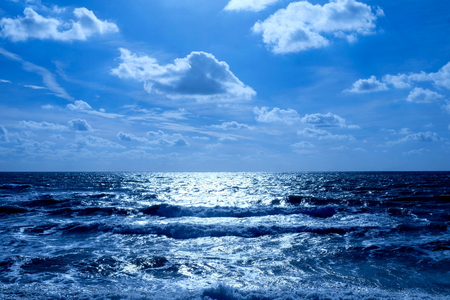 Foto de Sea and sky, in the bottom half is a deep blue sea with waves breaking, on the horizon is a line of white shimmering glowing light on the water in the upper half is the sky covered in fluffy clouds - Imagen libre de derechos