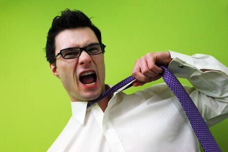 Frustrated businessman pulls at his tie and screams.