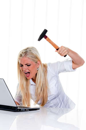 Furious businesswoman with hammer, yelling and preparing to smash her laptop. Vertical.