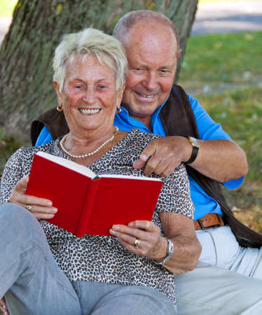 Mature couple in love senior citizens. Sitting in the park and read a book.