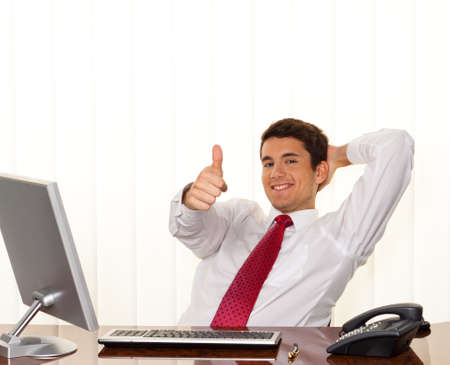A successful young manager sitting at a desk and smiles.