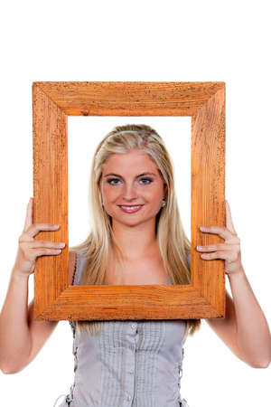 Young woman looks through a picture frame.
