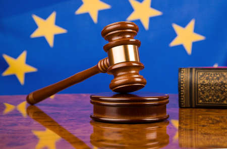 A gavel in court. With a European flag in the background.
