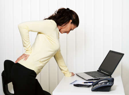 Woman with back pain of the intervertebral disc in office