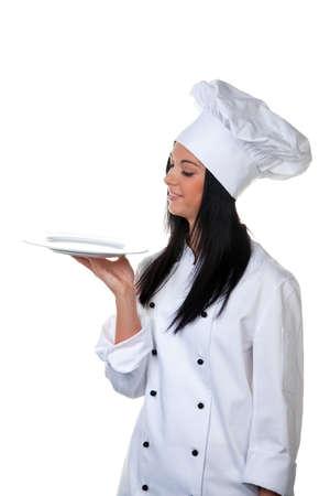 Young female apprentice chef presents a silver tray