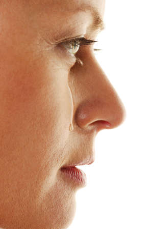 Woman is sad and cries. Teardrop on his cheek.