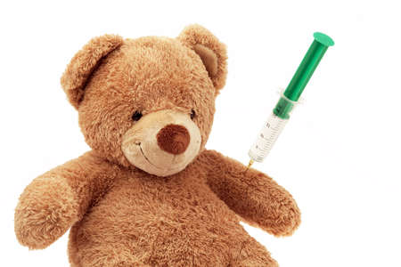 A Teddy gets an injection. Immunizations and syringe.