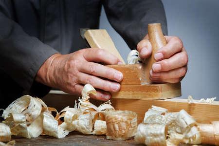 Photo pour A carpenter with a planer and wood shavings in the workshop. - image libre de droit