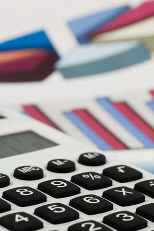 A calculator with graphics of a balance sheet. Sales, profit and operational costs.