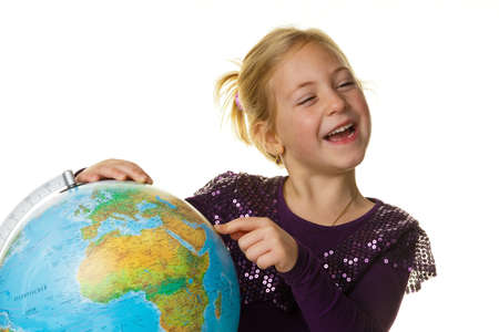 a little girl (child) looks at a globe.