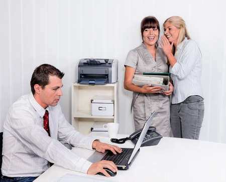 bullying in the workplace an office. two laugh about colleagues