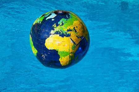 an inflatable globe floating in blue water  globalization