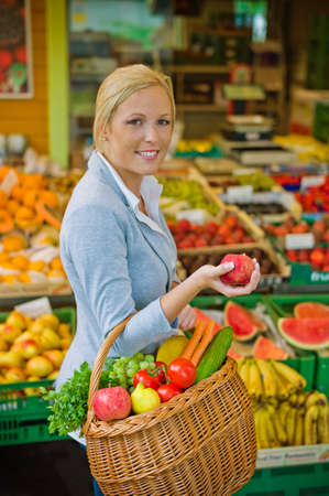 a young woman buys fruits and vegetables at a market  fresh and healthy food の写真素材