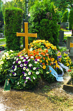 in a cemetery, a grave is fresh after a funeral
