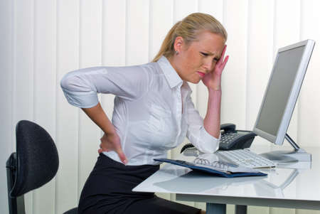 a woman with back pain from long sitting in the office  health and social welfare in the workplace