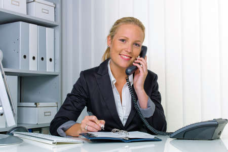 a friendly woman phoned at her desk in the office and record dates in the calendar