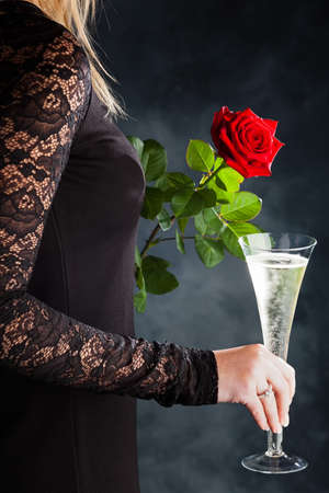 a woman in evening dress with a red rose and a glass of sparkling wine or champagne
