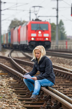 a young woman with suicidal thoughts sitting on a track  considers suicide note in his hand and thinks about her suicide