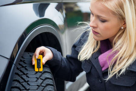 a young woman is measuring the tread depth of her car tire  the proper depth in the tread of a tire can prevent accidents