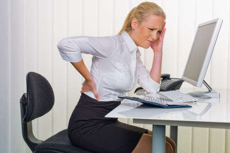 a woman with back pain from sitting so long in the office  health and welfare at work