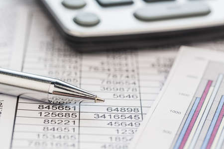 a calculator is on a balance sheet numbers are statistics  photo icon for sales, profit and cost