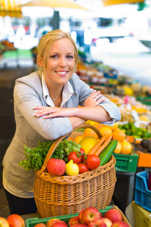 a young woman buying fruits and vegetables at a market  fresh and healthy food