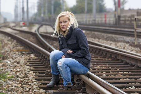 a young woman is sad, anxious and depressed  sitting on a track and is lonely