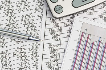 a calculator is on a balance sheet numbers are statistics  photo icon for sales, profits and costs