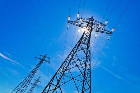 Photo pour a power mast of a high voltage transmission line against blue sky with sun - image libre de droit