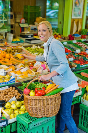a young woman buying fruits and vegetables at a weekly market  fresh and healthy diet