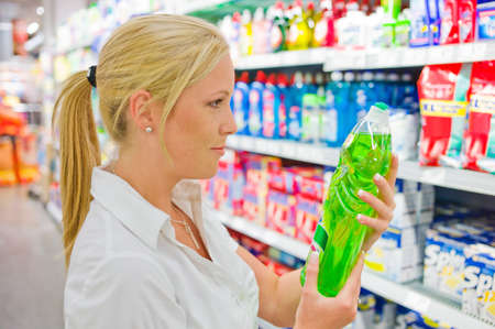 a woman buys cleaning supplies at a supermarket  shelf with cleaning agents