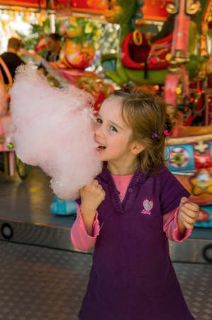 a girl has fun and i look at a fairground  and eating cotton candy
