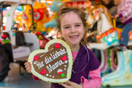 a little girl hÀt a heart made of gingerbread for the mother in her hand  symbol photo mother