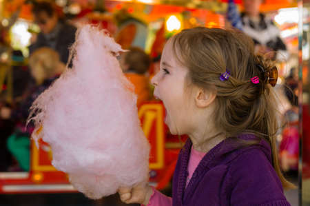 a little girl on a kirtag with cotton candy  fun and joy of fair