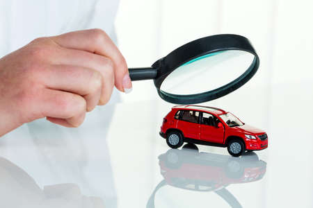 a model of a car is examined by a doctor. photo icon for workshop, service and car buying.