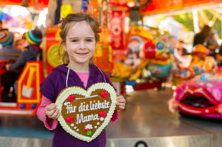 a little girl hold a heart made of gingerbread for the mother in her hand. representative photo mother