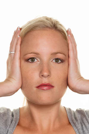 a young woman holding her ears. symbolic photo for not want to hear disputes and conflicts, as well as loud undtinnitus