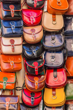Many different colorful handbags hanging for sale in a textile shop