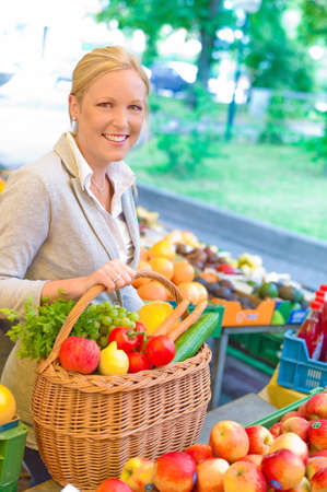 a young woman buying fruits and vegetables at a farmer's market. freshness and healthy diet.