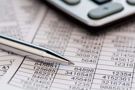 a calculator is located on the numbers a balance us statistics. photo icon for sales, profits and costs.