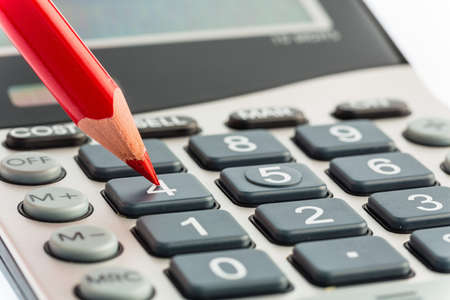 a red pen is on a calculator. save on costs, expenses and budget for bad economy