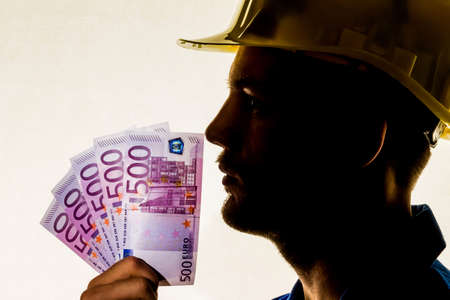 a worker in a business enterprise (craftsmen) with money bills in his hand