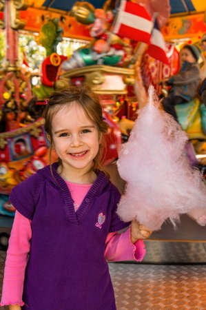 a girl has fun and look at a fairground. and eating cotton candy.