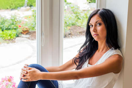 a young woman sitting on window and relaxes
